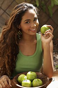 PictureIndia - Young woman with bowl of green apples smiling