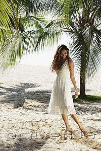 PictureIndia - young woman walking in the sand with coconut trees in background