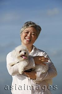 Asia Images Group - Older woman holding dog.