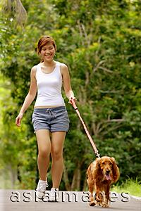 Asia Images Group - Young woman walking with her dog