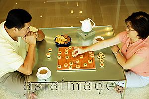 Asia Images Group - Couple sitting on floor, playing Chinese chess at home, high angle view