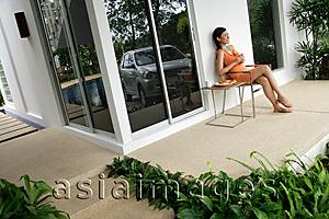 Asia Images Group - Woman at home, sitting and having coffee on patio