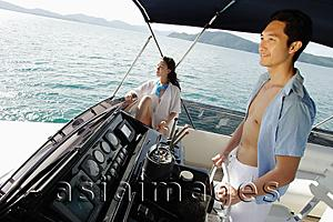 Asia Images Group - Couple on yacht, man steering, woman sitting, looking away