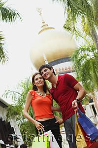 Asia Images Group - Couple standing side by side, mosque in the background