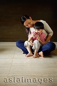 Asia Images Group - Mother with young son sitting on floor, boy drinking