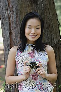 Asia Images Group - Young woman standing next to tree trunk, holding a camera, smiling