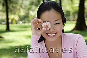 Asia Images Group - Young woman holding flower over eye