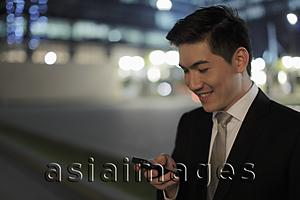 Asia Images Group - Man wearing a business suit, smiling at phone at night