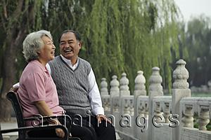 Asia Images Group - Older couple laughing at each other in a park