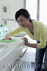 Asia Images Group - Young woman wiping a kitchen counter