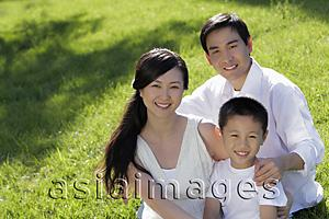 Asia Images Group - Young family sitting on grass smiling
