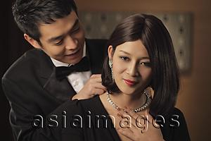 Asia Images Group - Young man putting a diamond necklace onto a woman