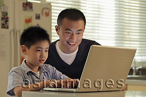 Asia Images Group - Father and son working on laptop computer together in kitchen