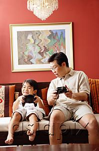 AsiaPix - Father and son sitting side by side on sofa, playing video game