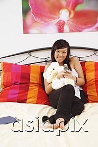 AsiaPix - Girl sitting on bed, hugging stuffed toy, using mobile phone, smiling at camera