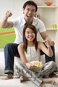 AsiaPix - Couple in living room, man sitting on sofa, woman on floor