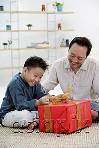 AsiaPix - Boy opening gift box, father next to him