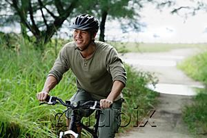 AsiaPix - Man cycling on nature path, smiling