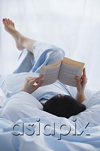 AsiaPix - Young woman lying in bed, reading a book