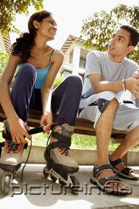 PictureIndia - Man and woman sitting on bench, woman lacing up roller blades
