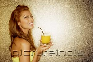 PictureIndia - Young woman holding drink, looking at camera, portrait
