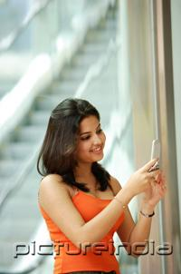 PictureIndia - Woman standing and holding mobile phone, smiling