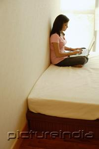 PictureIndia - Woman at home, sitting on bed, using laptop